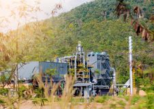 Przemysłowa roślina w zielonym drzewie i terenie górskim zdjęcie royalty free