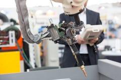 Przemysłowa spawalnicza mechaniczna ręka, zamazany operator w tle obrazy royalty free