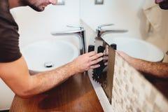 przemysłowego pracownika mozaiki intalling płytki i używać przemysłową kielnię w nowożytnej łazience zdjęcia royalty free