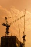 Przemysłowi budowa żurawie i budynek sylwetki nad słońcem Zdjęcie Royalty Free