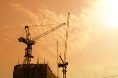 Przemysłowi budowa żurawie i budynek sylwetki nad słońcem Obraz Stock