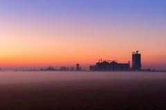 Przemysłowy mgłowy krajobraz, sylwetka stara fabryka przeciw zmierzchu niebu i mgła przy błękitną godziną przy nocą, Zdjęcie Stock