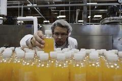 Przemysłowy pracownik egzamininuje butelkę w fabryce Zdjęcia Stock