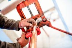 Przemysłowy pracownik używa przemysłowego miedzianego krajacza w instalaci wodnokanalizacyjnej zdjęcie stock
