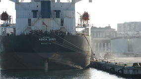 Przemysłowy statek dokujący przy molo portem podczas gdy buldożerów pracować zbiory
