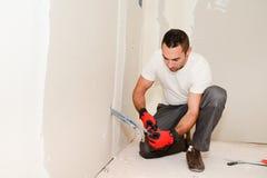 Przemysłu budowlanego elektryk odnawi elektryczną sieć w domowej budowie z narzędziami zdjęcia royalty free