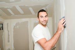 Przemysłu budowlanego pracownik gipsuje ściany i odnawi dom w budowie z narzędziami obrazy royalty free