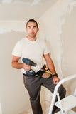 Przemysłu budowlanego pracownik odnawi dom w budowie z narzędziami i świderem fotografia royalty free