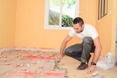 Przemysłu budowlanego pracownik odnawi dom z podłogowymi płytkami w budowie z narzędziami zdjęcia royalty free