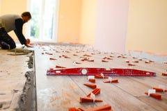 Przemysłu budowlanego pracownik odnawi dom z podłogowymi płytkami w budowie z narzędziami fotografia royalty free
