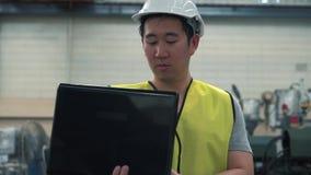 Przemys?owy in?ynier z ci??kim kapeluszem pracuje z laptopem przy fabryk? zbiory