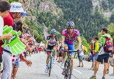 Przemyslaw Niemiec Climbing Alpe D'Huez. Alpe-D'Huez,France- July 18, 2013: Two cyclists,Przemyslaw Niemiec from Lampre Merida and Haimar Zubeldia from Royalty Free Stock Images