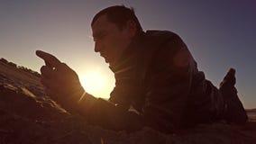 Przenośna konsola Mężczyzna kłamstwa na piasku i sztuki w przenośnej konsoli przy stylu życia zmierzchu światłem słonecznym Fotografia Stock