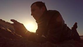 Przenośna konsola Mężczyzna kłamstwa na piasku i sztuki w przenośnej konsoli przy stylu życia zmierzchu światłem słonecznym Zdjęcia Royalty Free