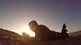Przenośna konsola Mężczyzna kłamstwa na piasku i sztuki w przenośnej konsoli przy zmierzchu światła słonecznego stylem życia Zdjęcie Stock