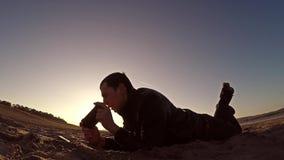 Przenośna konsola Mężczyzna kłamstwa na piasku i sztuki w przenośnej konsoli przy zmierzchu światłem słonecznym Zdjęcie Royalty Free