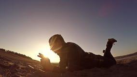 Przenośna konsola Mężczyzna kłamstwa na piasku i sztuki w przenośnej konsoli przy zmierzchu światłem słonecznym Obraz Royalty Free