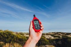 Przenośny termometr w ręce mierzy plenerową lotniczą temperaturę i wilgotność obraz royalty free