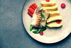 Przepasuje dorsz z kluchami, marchewkami, zieleń słodkim grochem i tomat, obraz stock