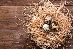 Przepiórek jajka na stosie słoma na drewnianym stole Zdjęcia Stock