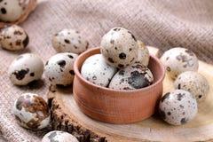 Przepiórek jajka w drewnianym pucharze na brown drewnianym stojaku na brown tle obraz stock