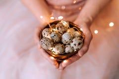 Przepiórek jajka w drewnianym talerzu w rękach dziewczyna na różowym tle zdjęcia royalty free