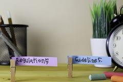 Przepisy i wytyczna Handwriting na kleistych notatkach w odzieżowych czopach na drewnianym biurowym biurku fotografia stock