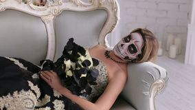 Przerażająca kobieta w sukni z makeup w postaci czaszki i kłama na retro kanapie zdjęcie wideo