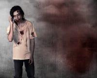 Przerażający męski żywy trup opowiada przez telefonu komórkowego Obrazy Royalty Free