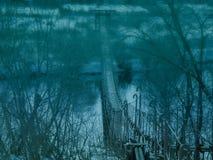 Przerażający stary zawieszenie most przez rzekę w mgle Temat dla Halloween fotografia royalty free