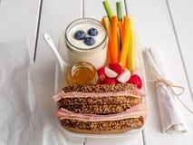 Przerwa chleba pudełko z świeżymi warzywami i baleron kanapką fotografia royalty free