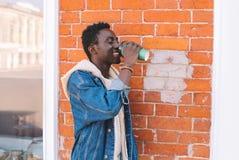 Przerwa czas! Szczęśliwy uśmiechnięty afrykański mężczyzna pije kawę na mieście fotografia stock