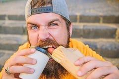 Przerwa uwalnia g?odu, pragnienia Brodaty m??czyzna ma i hot dog i kawy dla przek?ski przerwy Kaukaski facet cieszy si? fast food fotografia stock