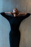 Przerzedże eleganckiej murzynki w pięknej zmrok sukni mienia szyi z rękami na szarym tle Fotografia Stock