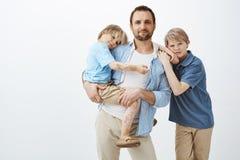 Przerzedże ojca z dwa ślicznymi dzieciakami stoi nad szarym tłem Tata trzyma małego syna w rękach i ono uśmiecha się szeroko zdjęcie royalty free