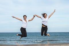 przeskakuje dwie dziewczyny plażowych zdjęcia stock