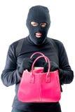 Przestępca z różową torbą w poszukiwaniu wartościowych rzeczy Zdjęcie Stock