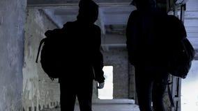 Przestępcy jest ubranym czarnego odprowadzenie w zaniechanym domu, przestępstwa planowanie, spisek fotografia stock