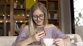 przestań tła rogalik filiżanki kawy sweet Żeński używa smartphone podczas gdy pijący kawę zdjęcie wideo