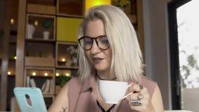 przestań tła rogalik filiżanki kawy sweet Żeński używa smartphone podczas gdy pijący kawę zbiory