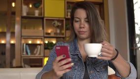 przestań tła rogalik filiżanki kawy sweet Żeński używa telefon komórkowy podczas gdy pijący kawę zbiory wideo