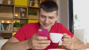 przestań tła rogalik filiżanki kawy sweet Mężczyzna używa telefon komórkowego podczas gdy pijący kawę zdjęcie wideo