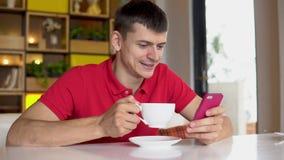 przestań tła rogalik filiżanki kawy sweet Mężczyzna używa telefon komórkowego podczas gdy pijący kawę zbiory wideo