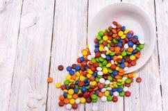 Przestawny talerz Rozlewający cukierek na stole obraz royalty free