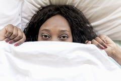 Przestraszona murzynka pod łóżkową koc obrazy royalty free