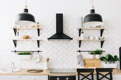 Przestronna nowo?ytna Skandynawska loft kuchnia z biel p?ytkami i czarnymi urz?dzeniami jasny pok?j nowoczesne wn?trze zdjęcia stock