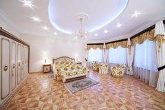 Przestronna sypialnia z pozłacanym dwoistym łóżkiem i wezgłowie stołami Zdjęcia Stock