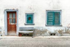 Przetarty i zatarty domu przodu szczegół z dwa okno i stara drewniana ławka na poboczu drzwi i chwiejne fotografia royalty free