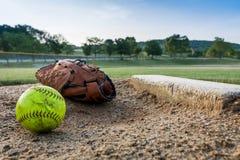 Przetarty softball i r?kawiczka na miotacza kopu w wczesnym poranku obraz stock