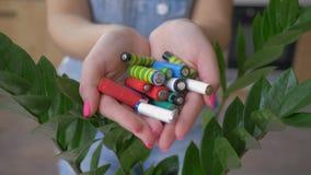 Przetwarzać i usuwanie, ręki trzyma alkalicznych baterii rozsypisko nad zielonym naturalnym tłem zdjęcie wideo